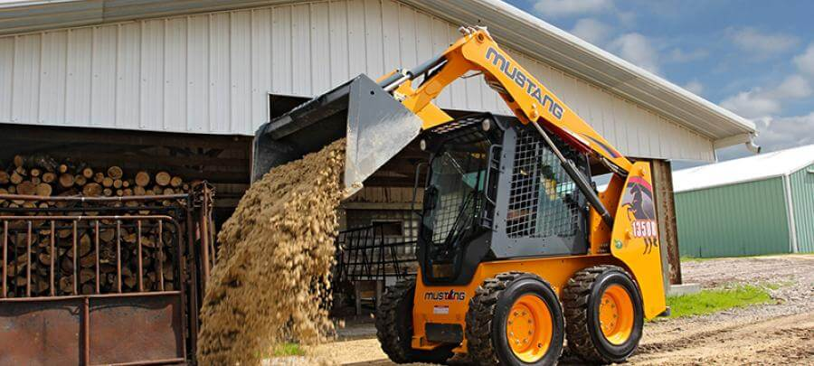 Mustang 1350R skid steer loader dumping dirt