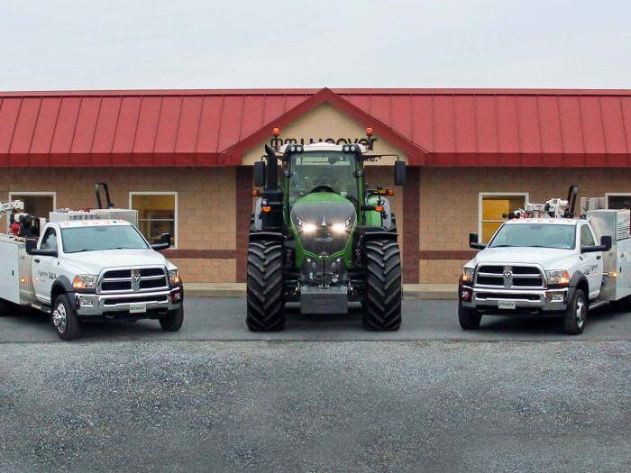 A Fendt tractor and service trucks sitting in front of the office.